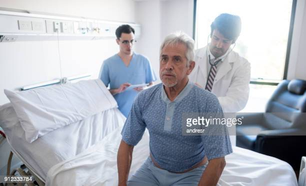 doctor checking a senior patients lungs at the hospital - respiratory system stock pictures, royalty-free photos & images