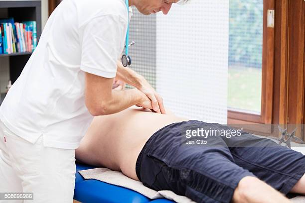 Doctor checking abdomen of mature patient