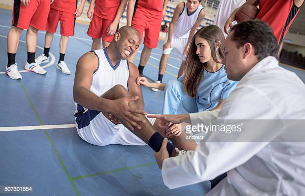 Doctor checking an ankle injury at a basketball game