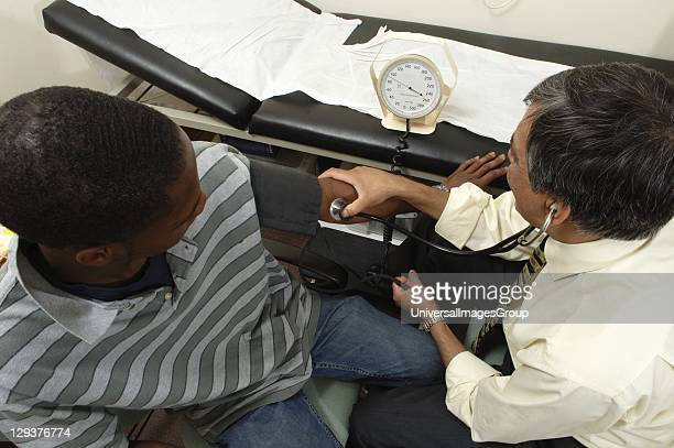 Doctor checking blood pressure of patient using sphygmomanometer
