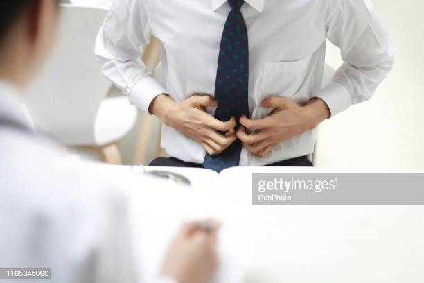 doctor checking businessman's stomach pain - uncomfortable stock pictures, royalty-free photos & images