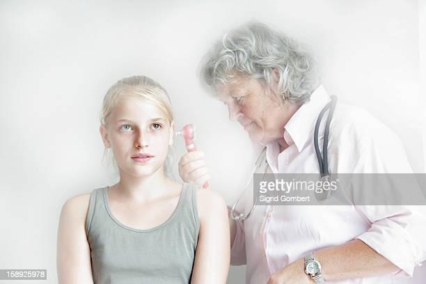 doctor checking girls inner ear - sigrid gombert imagens e fotografias de stock