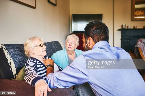 doctor checking heart beats of senior woman - house call stock pictures, royalty-free photos & images