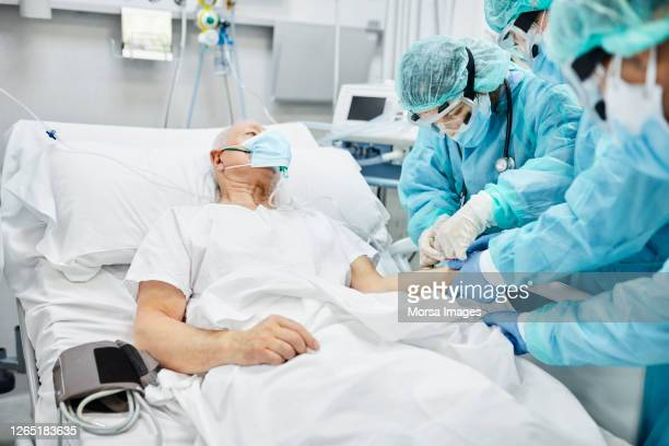 doctor checking iv level of patient after treatment - iv drip stock pictures, royalty-free photos & images