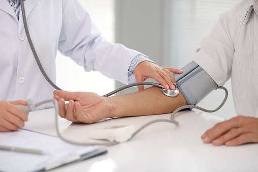 Doctor checking patients blood pressure on right arm 467555694