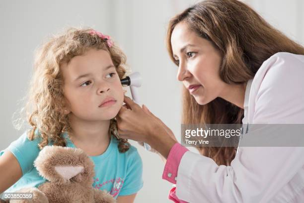Doctor checking patient's ears in office