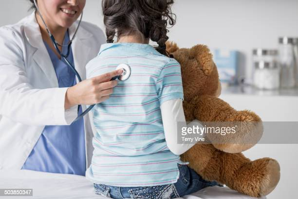 Doctor checking patient's heart beat