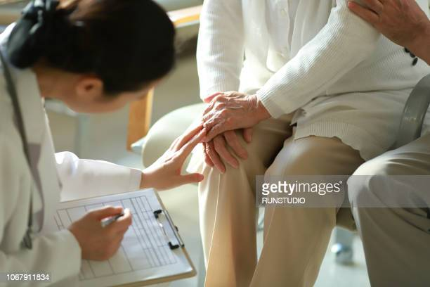 doctor checking patient's knee pain - human body part stock pictures, royalty-free photos & images