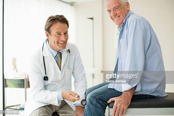 doctor checking patient's reflexes in doctor's office - knees together stock photos and pictures