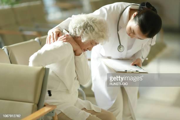 doctor checking  patient's shoulder pain - looking over shoulder ストックフォトと画像