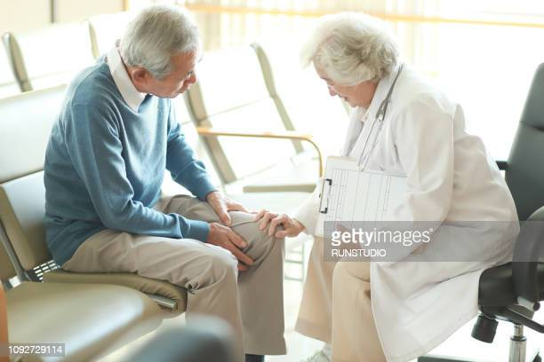 doctor checking senior patient's knee pain - human limb stock pictures, royalty-free photos & images