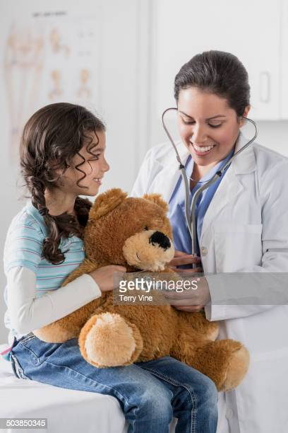 Doctor checking teddy bear's heart beat for patient