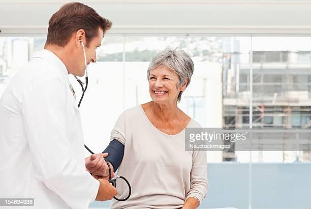 Arzt prüfen den Blutdruck einer älteren Patienten