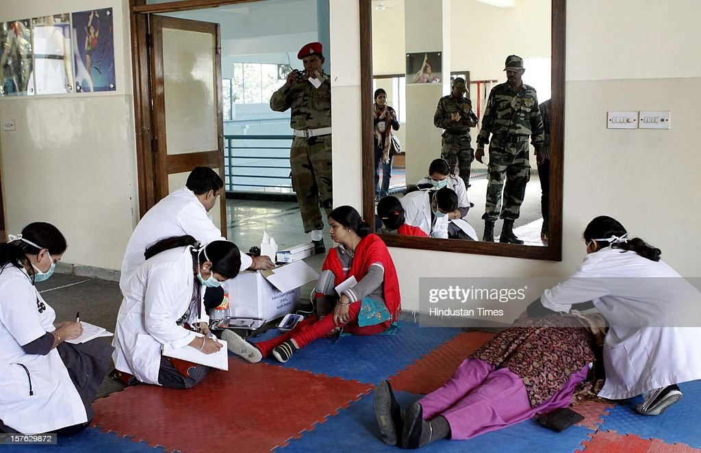 Doctor checking the injured patient during a mock drill held at Birla Vidya Niketan, South Delhi on December 4,2102 in New Delhi, India. Mock Drill performs at various place in the capital to test the alertness and responds during the time of emergency situation such as Earthquake, Fire, Bomb Blast.
