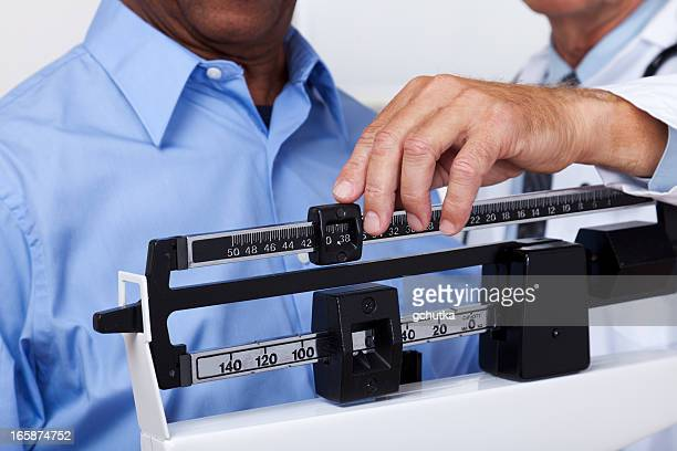 doctor checking weight - mass unit of measurement stock pictures, royalty-free photos & images