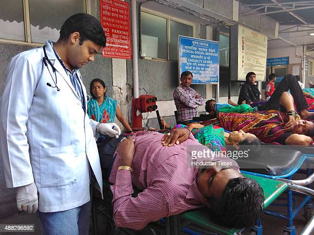 A doctor checks a patient on priority outside the emergency ward while others wait at AIIMS hospital's emergency ward as on September 15 2015 in New...