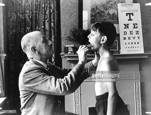 A doctor checks a young boy's tonsils December 1935 Founded in 1908 the School Medical Service provided many people's first experience of clinical...
