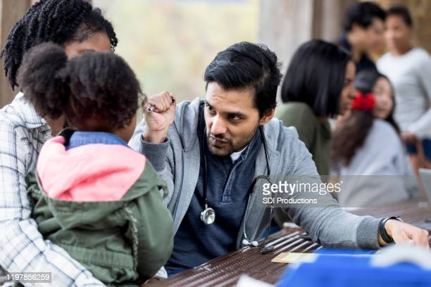 doctor checks child's eyes with light at free clinic - selfless stock pictures, royalty-free photos & images