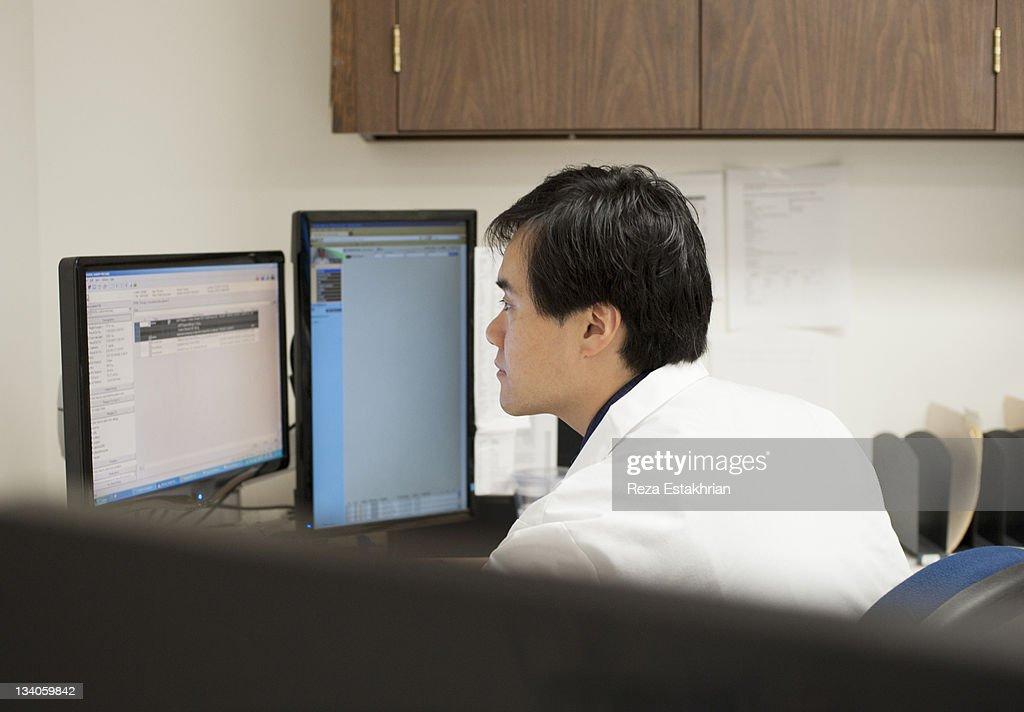 Doctor checks emails on computer : Foto de stock