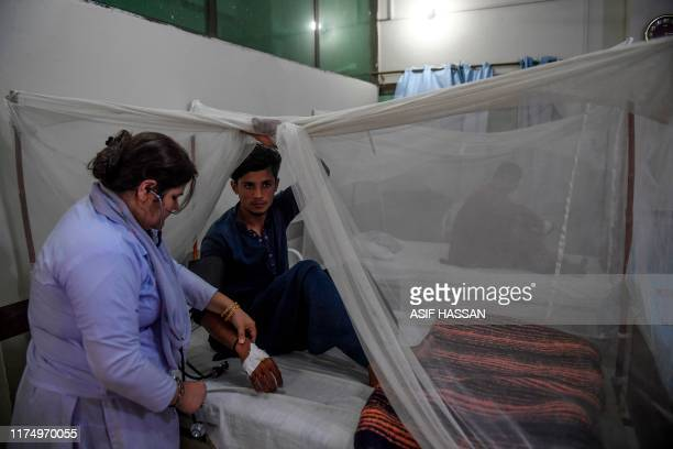 Doctor checks on a patient suffering from dengue fever under a net as he is treated at a government hospital in Karachi on October 10, 2019.