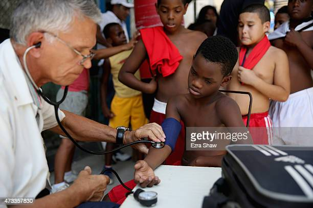 A doctor checks the blood pressure of a young boxer before a competition at Rafael Trejo Gym on May 8 2015 in Havana Cuba The Rafael Trejo Boxing Gym...