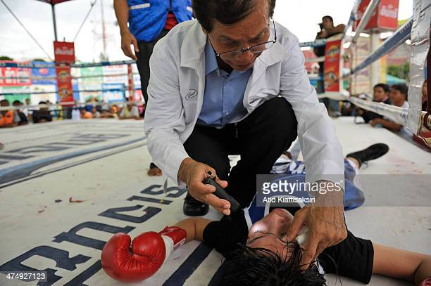 A doctor checks the reactions of a young girl boxer after she was knocked out during a Muay Thai fight