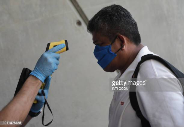 Doctor checks the temperature of a spectator upon arrival for the boxing evening at the Alexis Arguello Sports Center, in Managua on April 25, 2020....