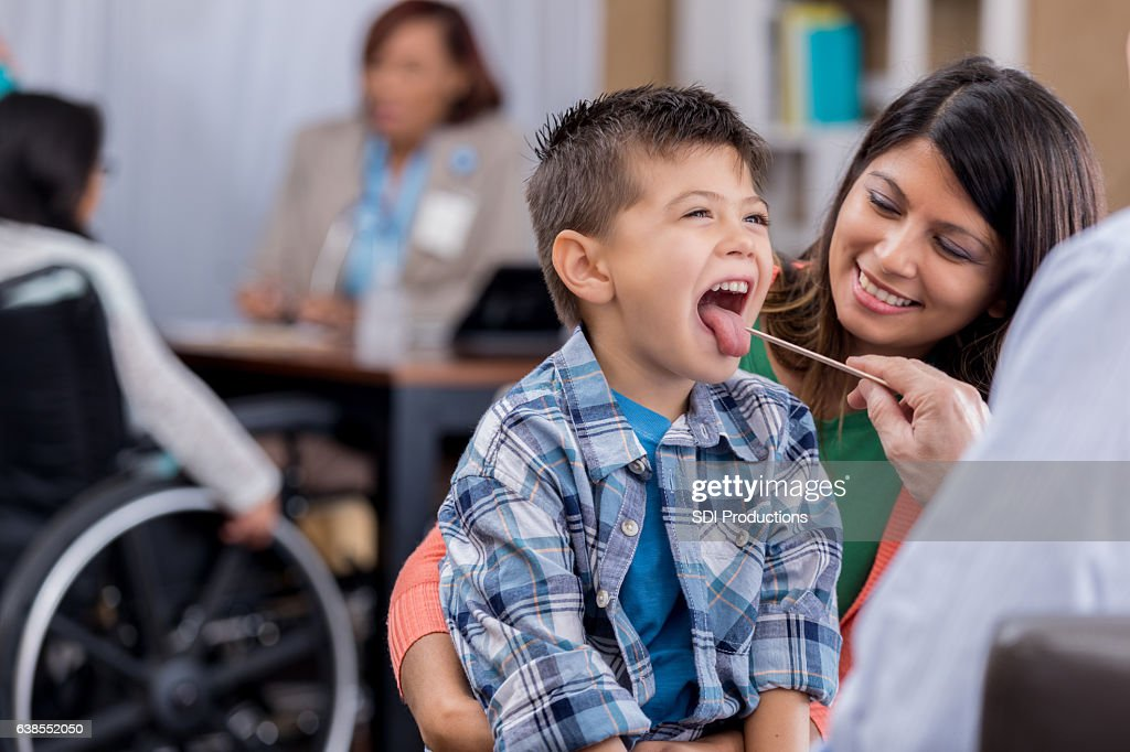 Doctor checks young patient's throat during exam : Stock Photo