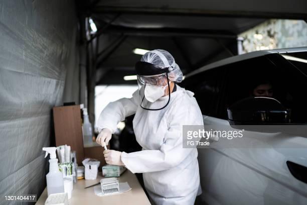 tubo de ensayo de cierre médico con hisopo de algodón para la prueba de covid-19 en el drive-thru - prueba de rodaje fotografías e imágenes de stock