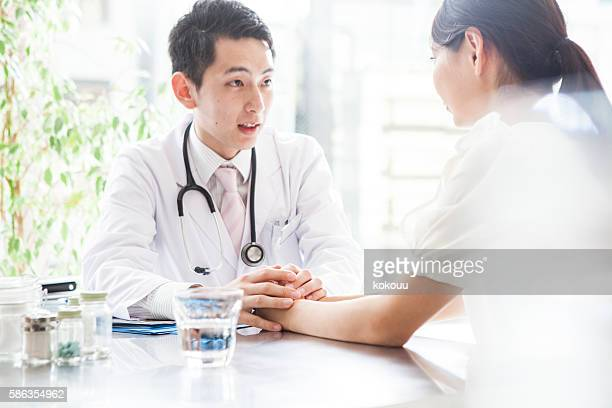 Doctor comforted while grasping the hands of the patient