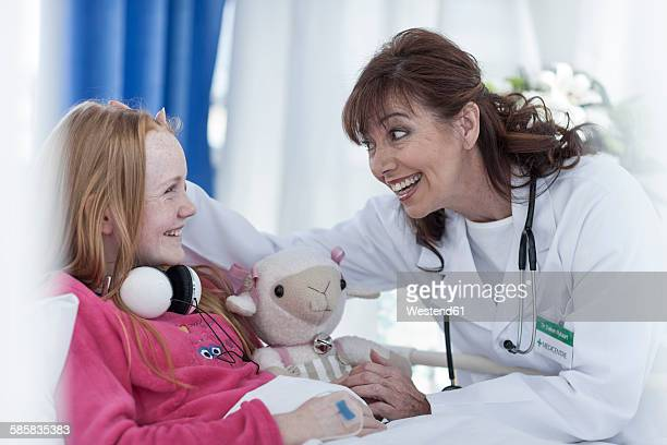 Doctor communicating with girl lying in hospital bed