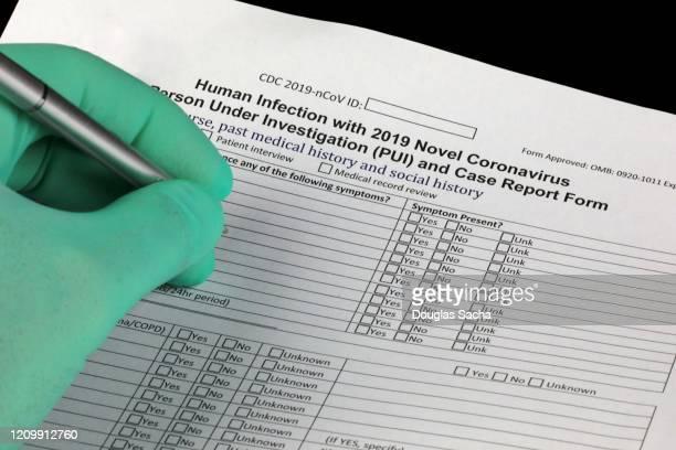 doctor completing the cdc form for reporting corona-virus investigation case report - centro per il controllo e la prevenzione delle malattie foto e immagini stock