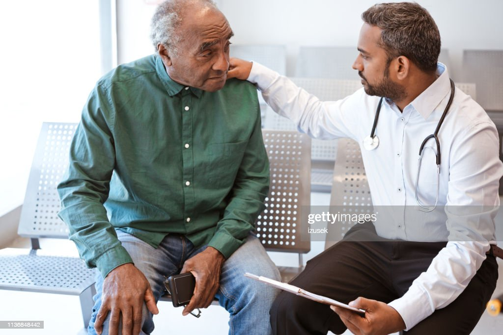 Doctor consoling sad senior male patient : Stock Photo