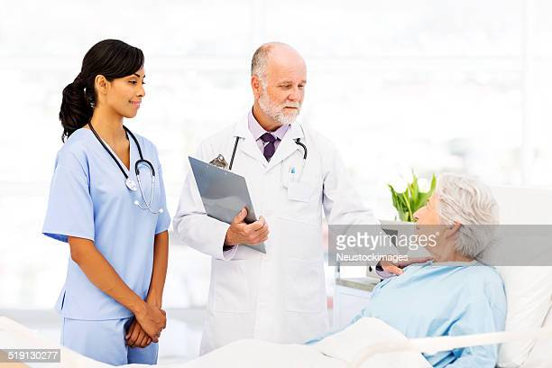 Doctor Consoling Senior Female Patient In Hospital Ward
