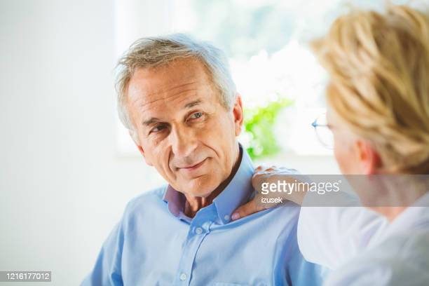 doctor consoling senior male patient - outpatient care stock pictures, royalty-free photos & images