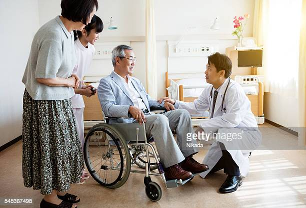 Doctor consoling senior man sitting on wheelchair with woman and