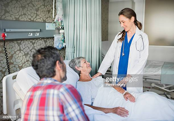 Doctor consulting a senior woman in hospital bed