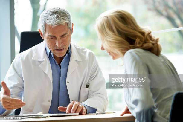 doctor consulting patient in clinic - patiënt stockfoto's en -beelden