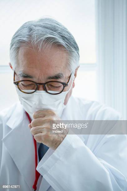 Doctor coughing and wearing protective mask