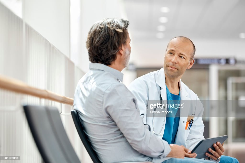 Doctor Counseling Male Patient In Waiting Room : Stock Photo