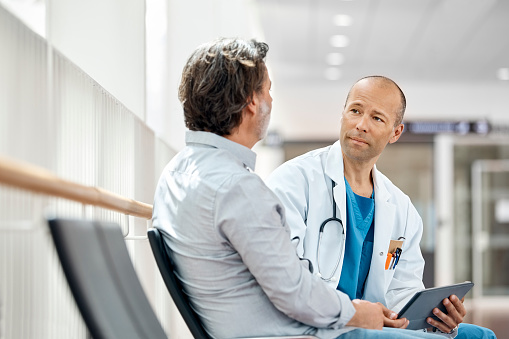 Doctor Counseling Male Patient In Waiting Room 985125958