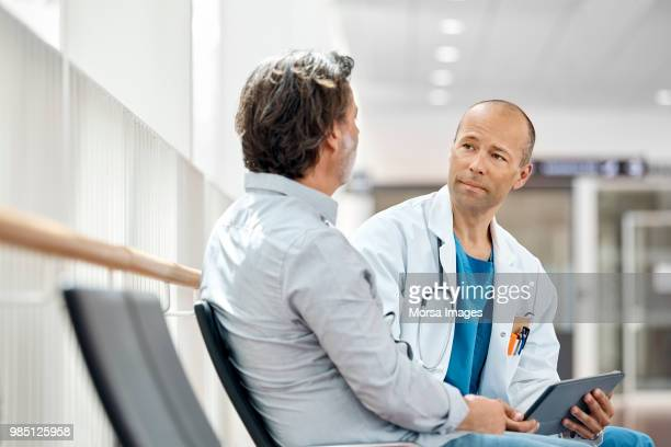doctor counseling male patient in waiting room - visita imagens e fotografias de stock