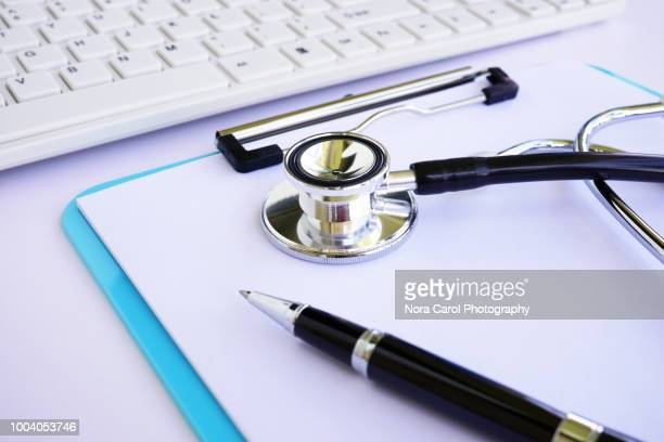 doctor desk - stethoscope, document, computer keyboard and pen - medicare stock pictures, royalty-free photos & images
