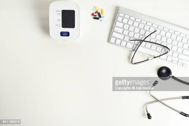 Doctor desk table with stethoscope, computer keyboard, eyeglasses, medical supplies top view with copy space flat lay