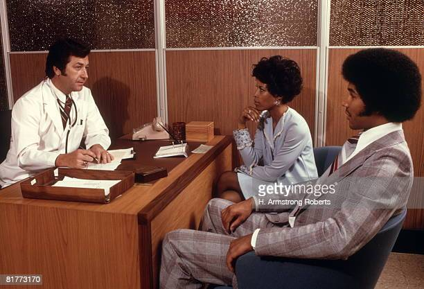 doctor desk talking to couple african-american man woman doctors office healthcare patient consultation. - afro amerikaanse etniciteit stockfoto's en -beelden