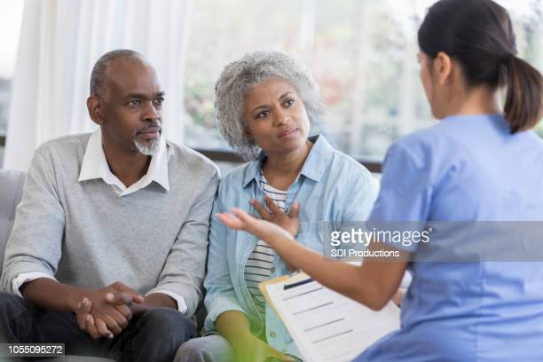 doctor discusses health concerns with senior couple - permission concept stock pictures, royalty-free photos & images