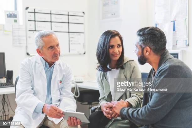 doctor discussing over digital tablet with couple - indian couples stock pictures, royalty-free photos & images