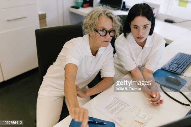 doctor discussing some scan results with mri technician - coinvolgimento dei dipendenti foto e immagini stock