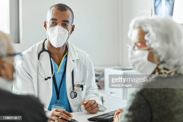 doctor discussing with couple during covid-19 - healthcare stock pictures, royalty-free photos & images