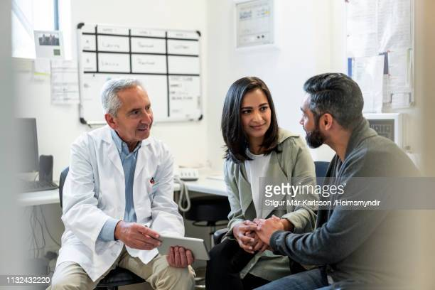 doctor discussing with couple over digital tablet - visita imagens e fotografias de stock